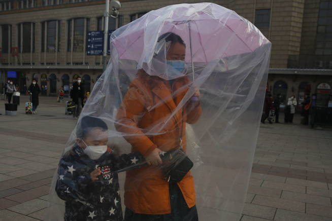 beijing-china-11-02-2020-a-passenger-wearing-protective-mask-and-holding-an-umbrella-to-hang-plastic-bags-to-cover-herself-and-her-chid-s-body-as-protection-from-coronavirus-at-beijing